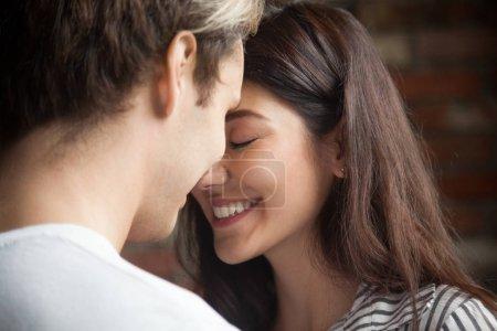 Photo pour Coup de tête de jeune couple romantique affectueux dans l'amour. Bouchent portrait de jolie jeune fille brune et le mec avec les yeux fermés, à proximité de l'autre. Concept de premier baiser, tendresse et amoureux - image libre de droit