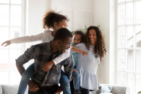 Photo for Playful laughing black family hugs with adorable little children have a fun standing in sitting room together at home. Black husband and wife preschool daughter and toddler son piggyback ride indoors - Royalty Free Image