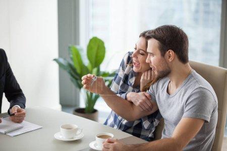 Photo pour Jeune couple heureux d'acheter, louer un nouvel appartement, maison. Mari avec les clés dans les mains. Clients satisfaits, clients. Conclusion d'un accord, conclusion d'un accord . - image libre de droit