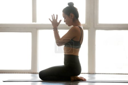 Photo for Young sporty attractive woman practicing yoga, doing seiza exercise, vajrasana pose with namaste, working out, wearing sportswear, grey pants, top, indoor full length, at yoga studio - Royalty Free Image