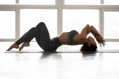 Young sporty yogi woman practicing yoga, Fish pose