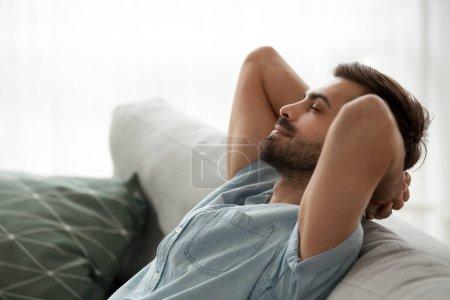 Photo pour Bouchent l'homme serein vue côté souriant assis sur le canapé à la maison. Mâle a une pause après le travail ou d'étude en fermant les yeux mettre les mains derrière la tête relaxant pense, se sent heureux de respirer le concept de l'air frais - image libre de droit