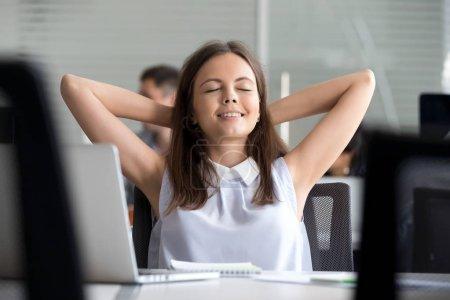 Photo pour Travailleuse d'affaires millénaire détendue prenant une pause travail terminé sur un ordinateur portable tenant les mains derrière la tête, calme jeune fille heureuse se reposant respirant l'air se sentant soulagement de l'esprit, aucun concept de travail sans stress - image libre de droit