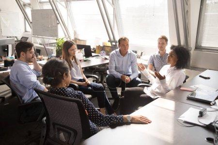 Photo pour Une enseignante coach leader africaine parle à des stagiaires d'équipe expliquant un nouveau projet discutant du plan d'affaires de l'entreprise lors d'une réunion de bureau multiraciale ou d'une formation d'entreprise sur les ventes . - image libre de droit