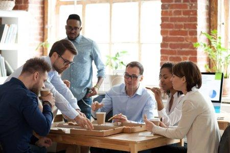 Photo pour L'équipe de travail multiraciale a la pause déjeuner au chat de travail appréciant la pizza délicieuse, divers collègues mangent le repas italien au bureau, les travailleurs commandent la livraison à emporter, goûtent la restauration rapide sur le lieu de travail communiquant - image libre de droit