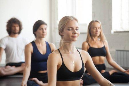 Photo pour Belle femme souriante et un groupe de jeunes sportifs pratiquant des cours de yoga, faisant Padmasana, pose Lotus avec les yeux fermés, travailler, fermer, studio. Concepts de mode de vie sains et conscients - image libre de droit