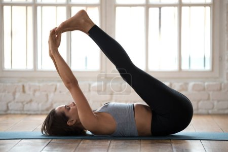 Young sporty attractive woman practicing yoga, Urdhva Prasarita