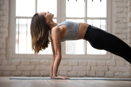 Photo for Young sporty attractive woman practicing yoga, doing Purvottanasana exercise, Upward Plank pose, working out, wearing sportswear, black pants and top, indoor close up, white yoga studio - Royalty Free Image