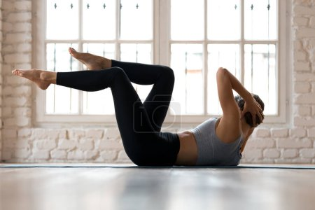 Photo for Young sporty woman practicing, doing crisscross exercise, bicycle crunches pose, working out, wearing sportswear, black pants and top, indoor full length, white sport studio - Royalty Free Image