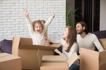 Photo for Happy family together in living room. Funny joyful young first time buyers playing with children. Little son jumping out of cardboard box. Buying real estate new house, relocating and mortgage concept - Royalty Free Image