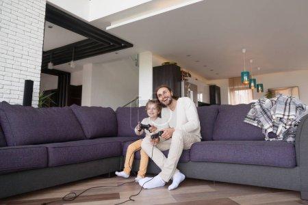 Photo pour Père drôle et petit fils préscolaire jouer à des jeux vidéo assis sur le canapé dans le salon à la maison, tenant joypad, s'amuser avec la console de nouvelle technologie en ligne. Week-end, temps libre avec concept de famille - image libre de droit