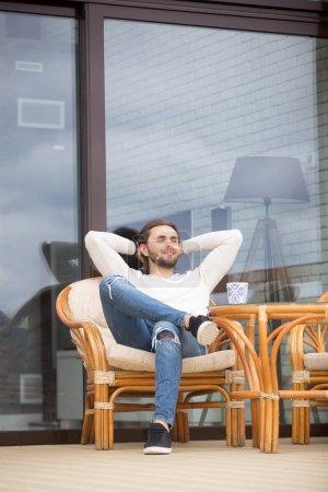 Photo pour Un jeune homme millénariste positif assis sur un fauteuil extérieur, les mains derrière la tête, respirant le repos et profitant de l'air frais du printemps face à une nouvelle maison moderne. Loisirs bonne journée réussi mâle - image libre de droit