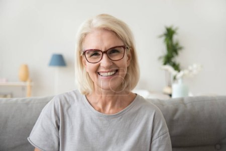 Photo for Smiling middle aged mature grey haired woman looking at camera, happy old lady in glasses posing at home indoor, positive single senior retired female sitting on sofa in living room headshot portrait - Royalty Free Image