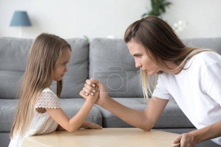 Sérieux maman et enfant fille bras de fer luttant ayant confrontation