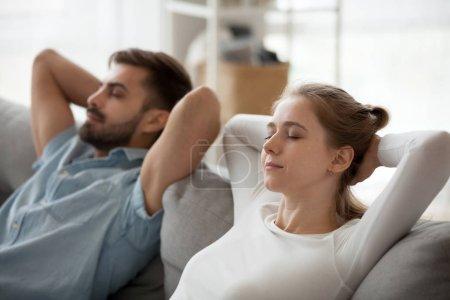 Photo pour Bouchent du Pacifique homme et femme se détendre sur confortable canapé à la maison les mains dessus de la tête, ayant à l'esprit millénaire couple allongé sur un canapé confortable au repos les yeux fermés, mari et femme sieste dans le salon - image libre de droit
