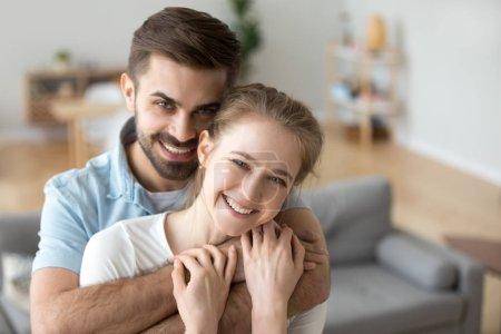 Photo pour Portrait de couple heureux millénaire étreinte regardant la caméra, mari souriant tenir dans les bras jeune femme bien-aimée posant dans le salon, headshot des acheteurs excités première fois faire photo de famille dans une nouvelle maison - image libre de droit
