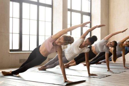 Photo pour Groupe de jeunes de divers peuples sportives, faire du yoga Vasisthasana exercent, planche côté pose, travail, intérieur pleine longueur, étudiantes de race mixte s'entraînant au club ou studio. Bien-être, mieux-être - image libre de droit