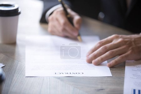 Photo for Man in suit fills name form and signs contract with a business partner, employment or insurance contract. Client signs the contract. Recruitment, hiring process human resources, close up view - Royalty Free Image