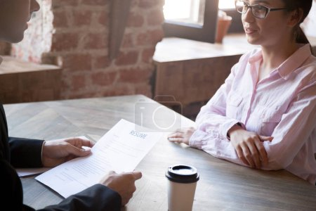 Photo for HR manager asks questions about resume to female applicant. Man in suit holds job interview with young woman. Hiring, staff recruiting process. Close up. - Royalty Free Image