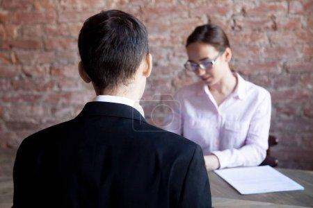 Photo pour Jeune homme à l'entretien d'embauche, femelle hr manager lecture résumé dans le fond. Demandeur en attente de décision. Embauche, processus, ressources humaines concept de recrutement de personnel. - image libre de droit
