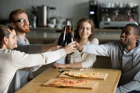 Photo for Diverse friends have fun in cafe toast say cheers, multiethnic students eat pizza and drink beer, clinking bottles excited celebrating meeting, millennial colleagues hang out in Italian restaurant - Royalty Free Image