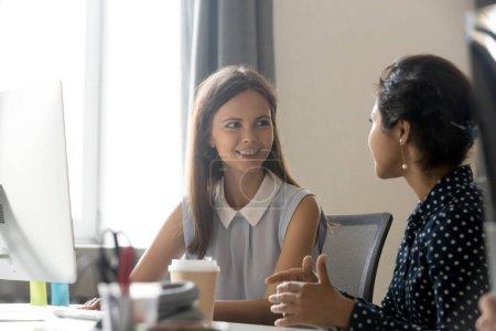Photo pour Jeune souriant employée écoute attentivement, parlant avec une collègue féminine sur lieu de travail, avoir une conversation agréable pendant la pause café, jeune femme discuter de nouveau projet, parler au bureau - image libre de droit