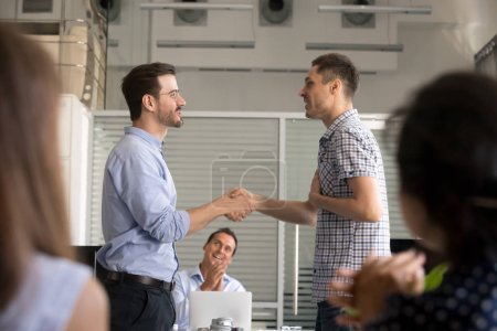 Photo pour Motiver le salarié de la poignée de main de chef d'équipe, de féliciter avec promotion, réalisation d'affaires, PDG de serrer la main, remercier pour le bon résultat, travail, exprimant respect, soutien, collègues applaudissent - image libre de droit