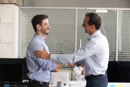 Photo pour Âge moyen sympathique patron salarié réussie de handshaking, féliciter travailleur confiant avec promotion, réussite de l'entreprise, remercier pour le bon travail résultats, exprimant respect, gratifiant - image libre de droit