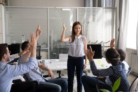Photo pour Jeune femme mentor, coach, tenant la formation pour le groupe de travailleurs de bureau, employés surélevé main prenant part à l'activité de construction d'équipe, les stagiaires, les collègues présentent une activité à répondre à la question du dirigeant - image libre de droit