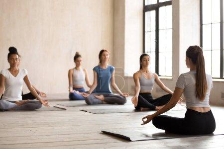 Photo pour Groupe de diversité multiethniques jeunes femmes assis en position du lotus sur des tapis à l'intérieur spacieux studio faisant des pratiques de méditation, mettant l'accent sur la vue arrière d'yoga instructeur. Concept de saines habitudes de vie active - image libre de droit