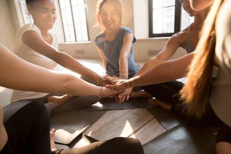 Photo pour Les jeunes filles diversifiées commencent une nouvelle journée avec le sport rassemblé dans un studio de fitness assis en cercle sur des tapis de yoga mettant leurs mains ensemble montrant l'unité travail d'équipe et de soutien, la lumière du soleil à travers les grandes fenêtres - image libre de droit