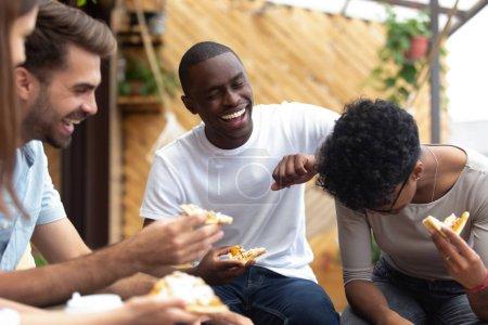 Photo pour Heureux amis multiethniques manger de la pizza, malbouffe italienne ensemble dans un café, rire de blague, nouvelles drôles, s'amuser ensemble à la réunion, collègues excités partager le repas au déjeuner, traîner ensemble - image libre de droit