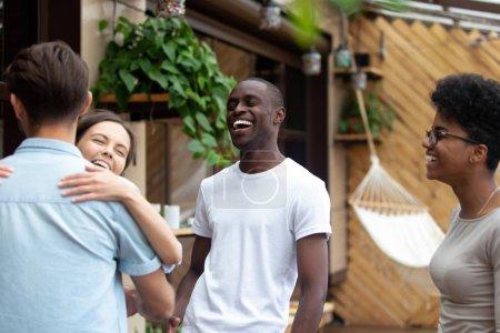Photo pour Heureux amis rieurs embrassant au hasard réunion après longtemps, excités personnes multiethniques, homme et femme s'embrassant dans le café, bonnes relations, collègues s'amusant ensemble - image libre de droit