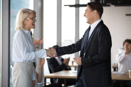 Photo for Middle aged excited employee getting reward shake hands with company boss. Executive manager congratulates best worker of the month handshaking with happy experienced colleague standing in coworking - Royalty Free Image