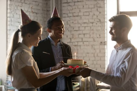 Diverse employees in party hats holding gifts congratulating cow