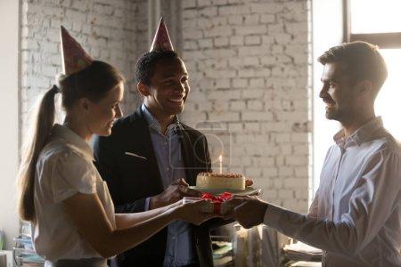 Diverse Mitarbeiter in Parteimützen mit Geschenken zum Gratulieren