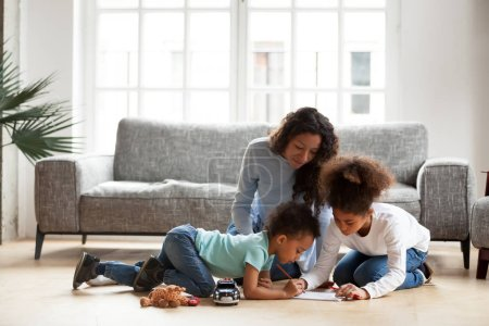 Photo for Loving black mom and little mixed race children drawing with colored pencils in living room, happy single african mum helping kids with creative activity at home, underfloor heating, family hobbies - Royalty Free Image