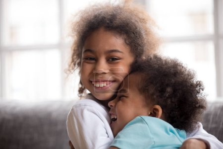 Photo for Happy african girl sister embracing little boy brother looking at camera, 2 funny mixed race preschool kids hug portrait, black children cuddling laughing, two siblings friendship good relationships - Royalty Free Image