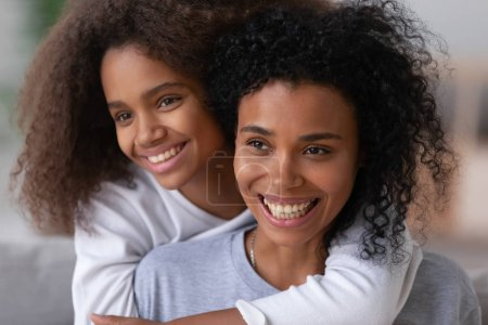 Photo for Portrait of smiling African American young mom and teenage daughter posing for family picture together, black teen girl piggyback happy mother or nanny enjoying free time, laugh or have fun - Royalty Free Image