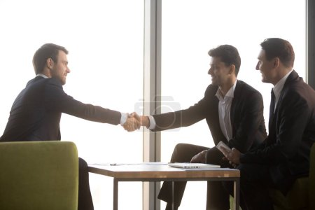 Photo for Happy arabic and caucasian businessmen in suits shaking hands after successful negotiation at meeting, diverse partners making business deal, promising loyalty starting collaboration, respect concept - Royalty Free Image