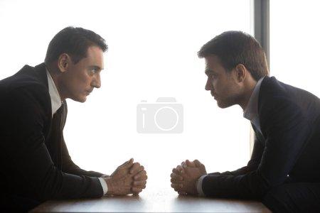 Photo pour Deux hommes d'affaires confiants avec les mains jointes se regardent assis en face comme concept de confrontation de rivalité, adversaires commerciaux concurrents politiciens débat, négociations difficiles, vue de côté - image libre de droit