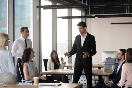 Photo pour Chef de l'équipe masculine arabe PDG président parler à des gens d'affaires diversifié à réunion de bureau, groupe multiethnique employés écouter arabe entraîneur mentor parler expliquer de nouveau projet à la formation du personnel - image libre de droit