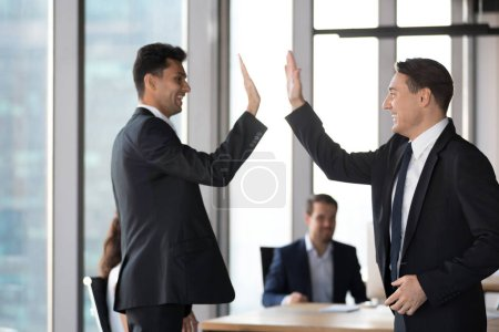 Photo for Happy excited arabic and caucasian executive in suits giving high five in office motivated by business success celebrating victory, achievement win or successful deal, support, good result concept - Royalty Free Image