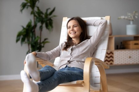 Photo for Happy calm young woman relaxing on comfortable wooden rocking chair in living room, smiling millennial girl having fun resting in armchair at home feeling stress free enjoying healthy weekend - Royalty Free Image