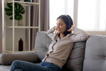 Calm young woman wearing headphones listening good...
