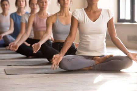 Photo pour Tons multiraciales jeunes femmes s'asseoir en position du lotus pratiquer l'yoga en studio de remise en forme ensemble, ajustement calme divers yogi assis dans la rangée méditer sur des nattes en caoutchouc avec des mains mudra. Concept de mode de vie sain - image libre de droit