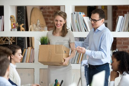 Photo for Excited new employee holding box get acquainted with team on first day concept, friendly executive ceo introducing welcoming female intern newcomer supporting hired corporate worker starting work - Royalty Free Image