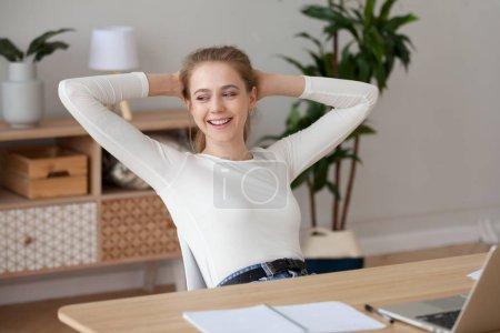 Photo pour Heureuse étudiante satisfaite de se détendre terminé le travail ou d'étudier à la maison, souriante fille tenant les mains derrière la tête assis au bureau prendre une pause pour se reposer après le travail bien fait ne jouissant d'aucun soulagement sans stress - image libre de droit