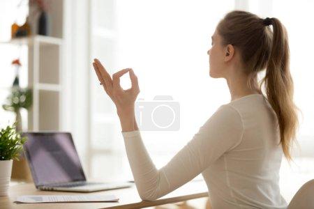 Photo pour Sereine femme calme en bonne santé, assis au bureau, faire des exercices d'yoga de relaxation ou de concentration au travail, méditation de bureau au travail ne gestion aucune détente libre, paix du concept de l'esprit, vue arrière - image libre de droit