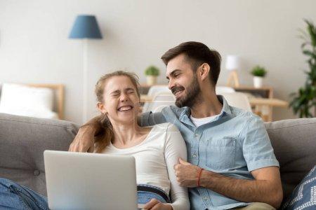 Photo pour Heureux jeune couple riant de plaisanterie drôle se détendre sur le canapé avec ordinateur portable, famille joyeuse profiter week-end avec dispositif, homme joyeux et femme jouissant rire sincère s'amuser avec l'ordinateur à la maison - image libre de droit